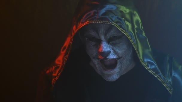 Detail, chlap s vlkem Vlk na tvář v černé kápi napodobuje zvířecí řev v zakouřené Studio