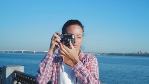 Detailní záběr krásná žena vypadá do hledáčku retro fotoaparát a fotka