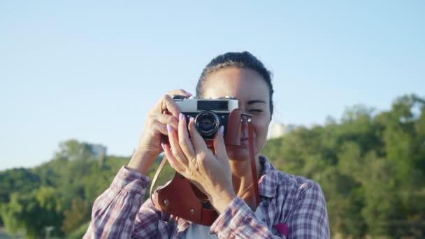 Detailní záběr portrét krásné ženy s retro kamerou na mostě