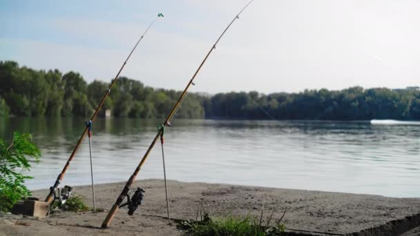 Horgászbot áll a parton a folyó hátterében