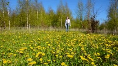 Young girl walks on a meadow