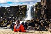 Fényképek fiatal lány az Izlandi vízesés közelében hűtés