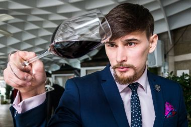 Young sommelier offers red wine