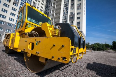 Yellow road roller works on construction site construction site