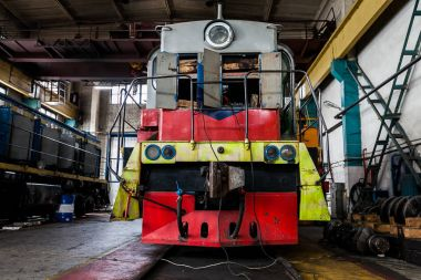 a large old Russian locomotive is in depot for repairs