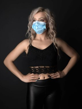 Beautiful blonde woman with long curly hair with respirator mask