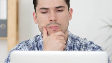 Pensive Creative Man working Online, Front View