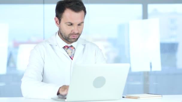 Arzt tippt auf Laptop im Krankenhaus, rothaarig