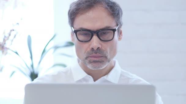 Mann, Blick in die Kamera während der Arbeiten am Laptop, Close Up
