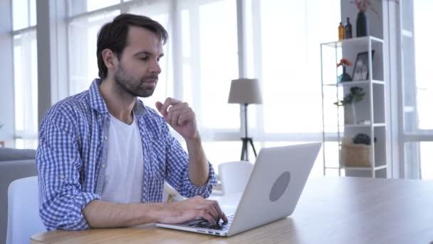Nachdenklich lässig Bart Mann denken und arbeiten am Laptop