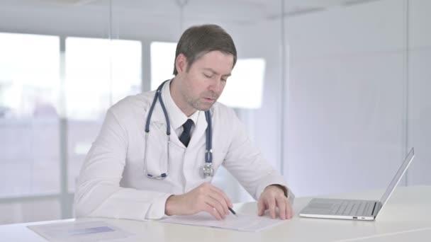 Vážný středověký lékař dělá papírování v kanceláři