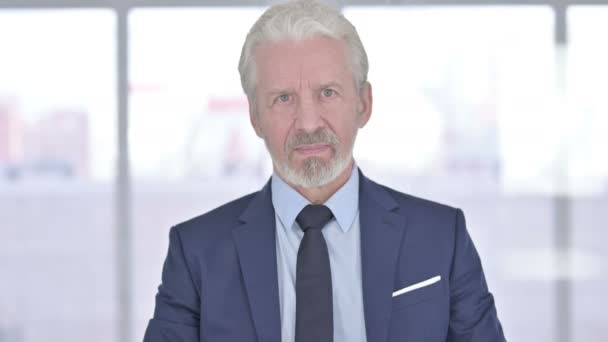 Porträt eines alten Geschäftsmannes, der im Amt Daumen hoch macht