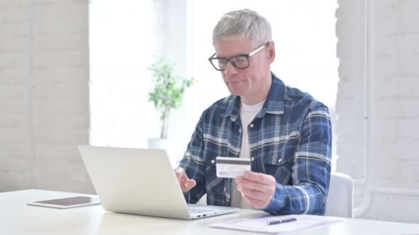 erfolgreiche Casual mittleren Alters Mann macht Online-Zahlung auf Laptop