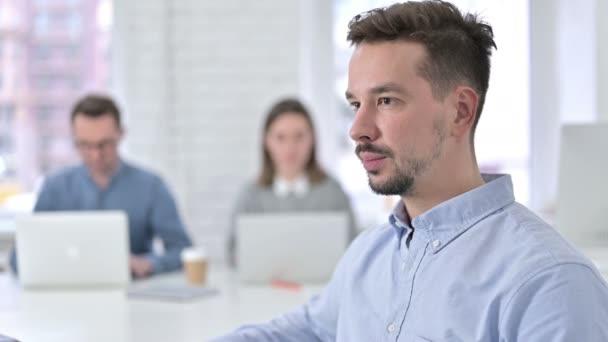 attraktiver junger Mann lächelt im Büro in die Kamera