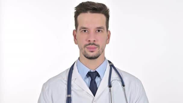 Porträt eines jungen männlichen Arztes, der in die Kamera blickt, weißer Hintergrund