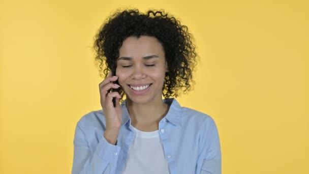 Porträt einer fröhlichen Afrikanerin, die auf dem Smartphone spricht