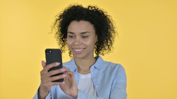 Porträt einer attraktiven afrikanischen Gelegenheitsfrau mit Smartphone