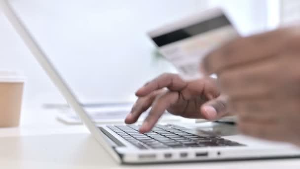 Nahaufnahme der Hände eines Afrikaners, der online am Laptop bezahlt