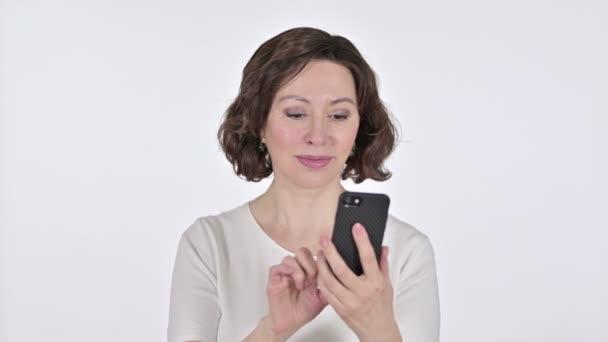 Alte Frau feiert auf Smartphone, weißer Hintergrund