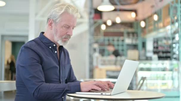 Alter Mann mit Laptop lächelt in Kamera im Cafe