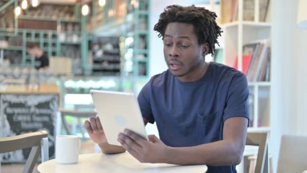 African Man Celebrating on Tablet in Cafe, Success