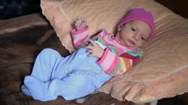 Postaven na postel miminko s modrýma očima směrem dopředu podivně
