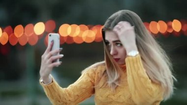 Young woman is preening, looking in reflection on smartphone Against the background of yellow lights