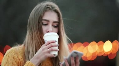 Beautiful blond drinks coffee and talks on the mobile Against the background of yellow lights