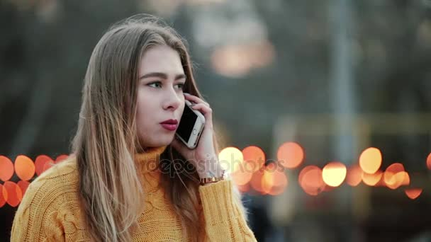 Portrait Beautiful woman is talking on the mobile background of yellow lights wind blows in city