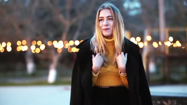 Beautiful blonde woman sits in a coat, looks around, waits, then laughs background of yellow lights