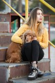 Photo Beautiful blonde looking like Jennifer Aniston sitting with a Cocker Spaniel dog on a metal stairway