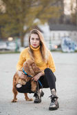 Photo Beautiful blonde looking like Jennifer Aniston is siting with dog against backdrop of urban homes