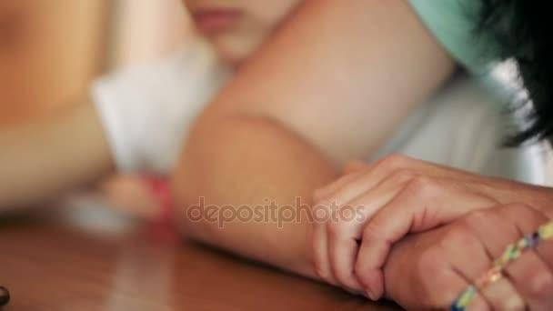 kleines Mädchen, das mit seiner Mutter in einem Café sitzt, traurig, träumend. Er umarmt Mama an der Hand. Nahaufnahme