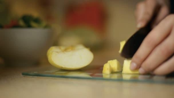 Mladá žena dívka plátky jablka na skleněné desce v kuchyni