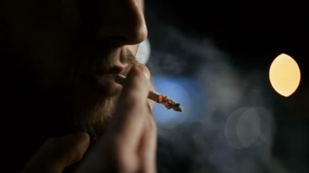 Fiatal srác kívül áll az éjszakai város őszén, és dohányzik a felkészülés rázza a hamu