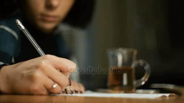 Young woman sitting cafe outdoors autumn Wrapped in blanket She signs the document writes a pencil