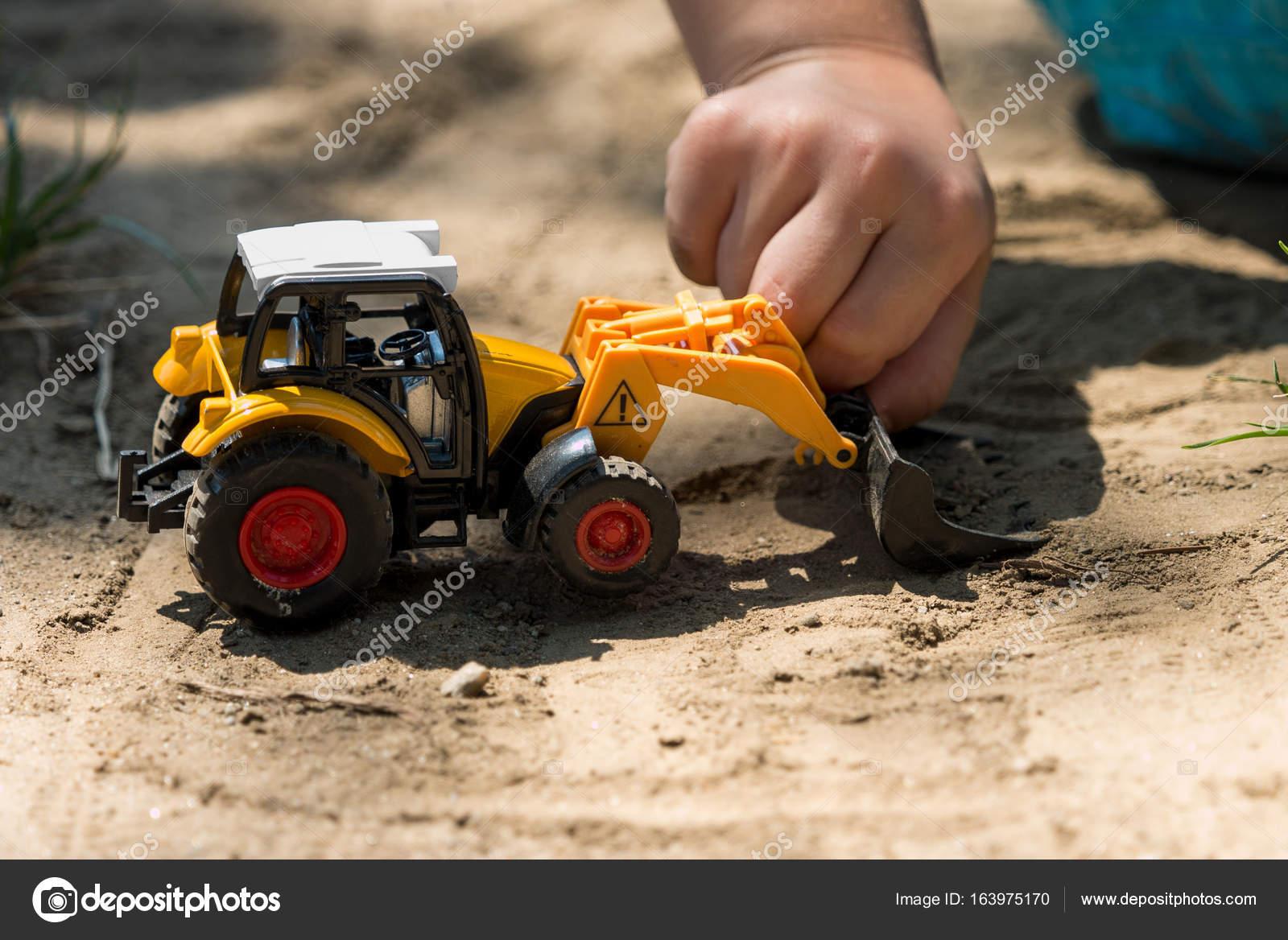 Kinder spielen mit traktor spielzeug in sand u stockfoto