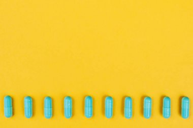 Green pills on a yellow background close-up top view, help with illness with place for text