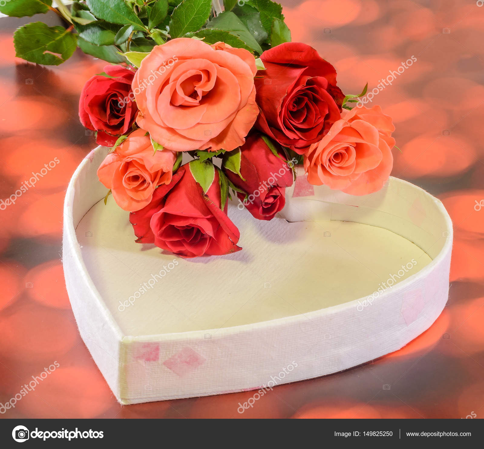 Red and orange roses flowers with heart shape gift box, red