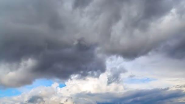 4k Zeitraffer. Dramatische Bewegung der Gewitterwolken im zeitigen Frühling vor dem Hintergrund des blauen Himmels