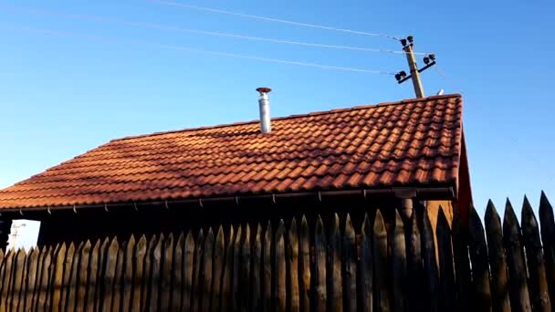 Fence made of sharp wooden stakes. Wooden houses with red tiled roof and blue clear sky. Sunny day