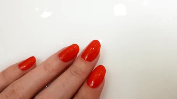Červené nehty, klasická manikúra, ženská ruka na bílém povrchu s vodou, lázeňský den