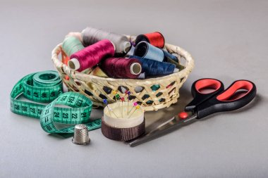 items for sewing, thread, needles, scissors in the basket