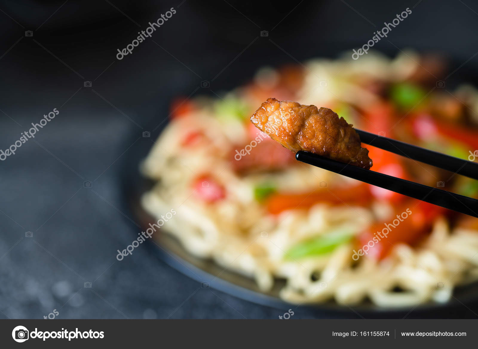 Szechuan stir fried spicy pork hold with chop sticks  Chinese fo