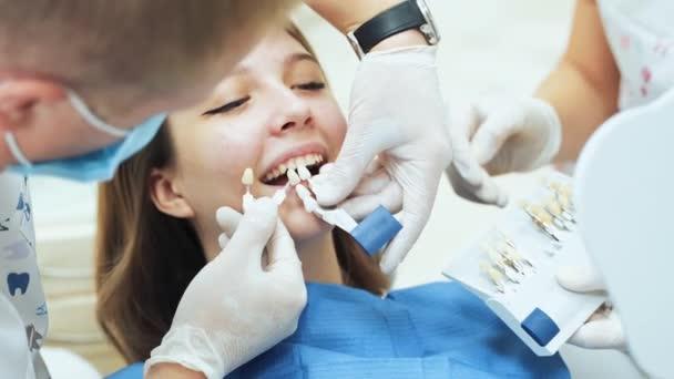 Zubař v lékařských rukavicích s asistentem, který zkouší protézy pro mladou dívku. Paleta odstínů zubů pro zubní protézy vitaskale.