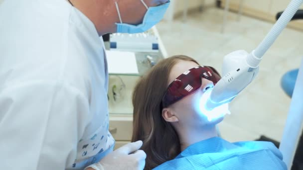 Zubní lékař vypne zařízení pro bělení laserových zubů. Dívka v červené ochranné brýle v křesle na zubní klinice
