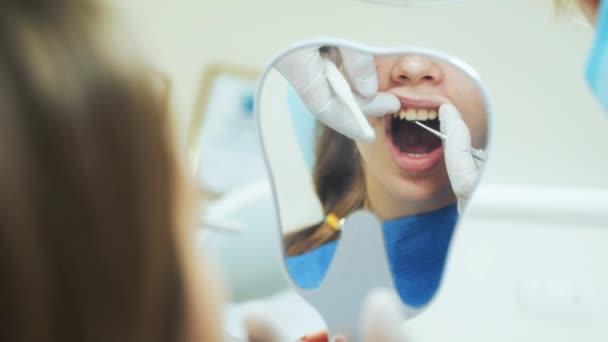 Zubní lékař vyšetřuje zuby pacientky. Dívka drží zrcadlo ve svých rukou.