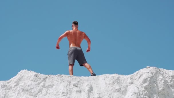 Bodybuilder athlete posing with muscles in nature against a blue sky. A man stands with his back.