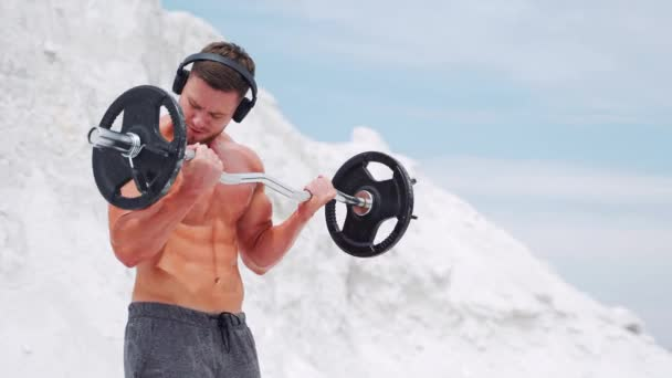 A man in headphones does barbell biceps exercises. Workout in nature.