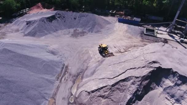 Eine Planierraupe sammelt Trümmer. Das Gebiet des Granitbruchs, von oben mit dem Hubschrauber.